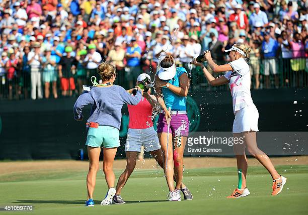 Michelle Wie of the USA is drenched with champagne by Jessica Korda Jaye Marie Green and Jamie Kuhn after holing the winning putt at the par 4 18th...