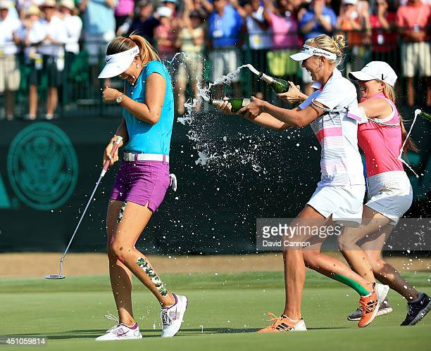 Michelle Wie of the USA is drenched with champagne by Jessica Korda and Jamie Kuhn after holing the winning putt at the par 4 18th hole during the...