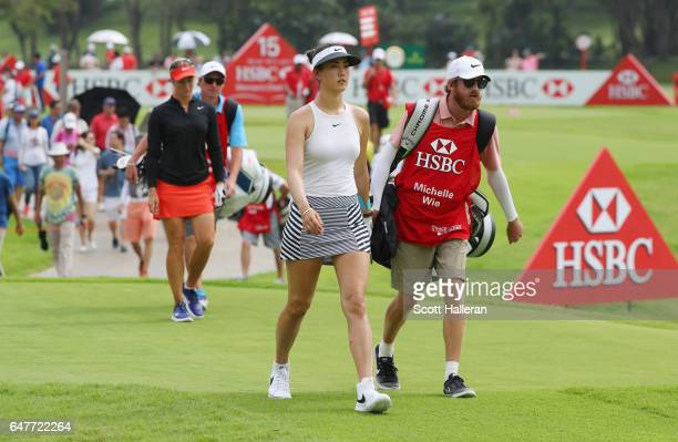 Michelle Wie of the USA walks with her caddie on the 15th hole during the third round of the HSBC Women's Champions on the Tanjong Course at Sentosa...