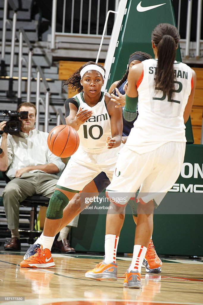 Michelle Woods #10 of the Miami Hurricanes passes the ball to Morgan Stroman #32 during action against the Penn State Lady Lions on November 29, 2012 at the BankUnited Center in Coral Gables, Florida. Miami defeated Penn State 69-65.