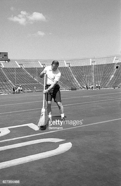 Michigan coach Bo Schembechler proves that lawnmowers are a thing of the past at the University football stadium 8/26 as he sweeps clean the...