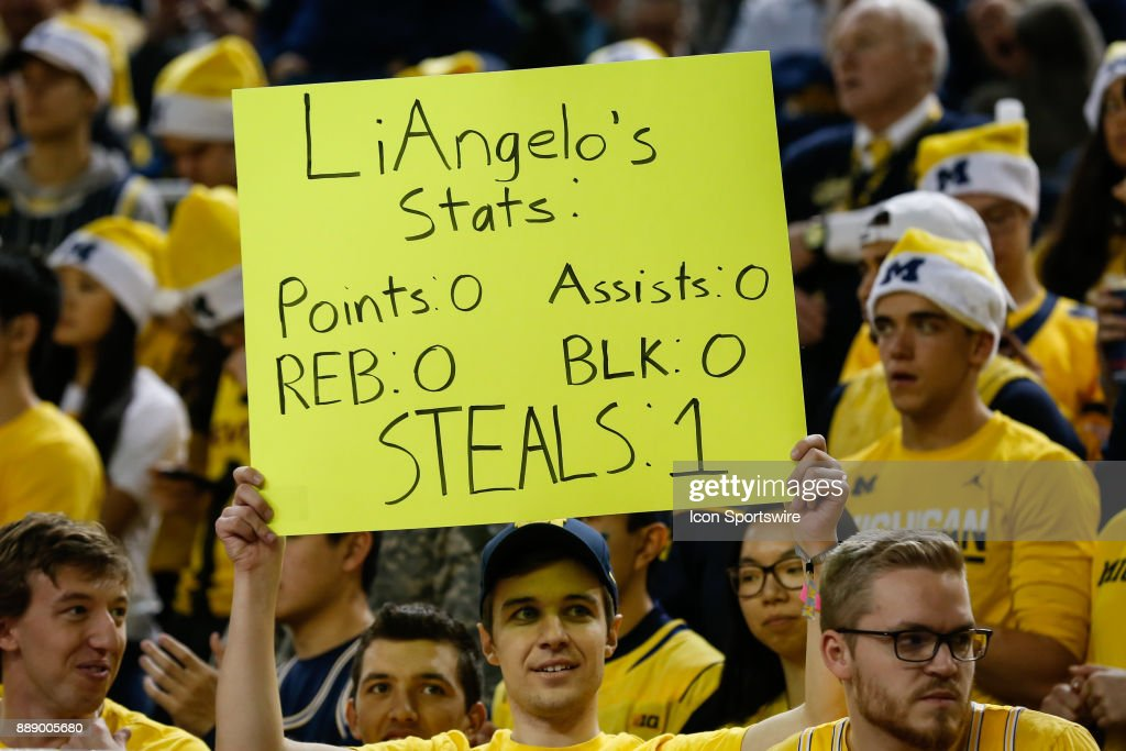 A Michigan fan holds a sign stating former UCLA Bruin LiAngelo Ball's season statistics during the second half of a regular season non-conference basketball game between the UCLA Bruins and the Michigan Wolverines on December 9, 2017 at the Crisler Center in Ann Arbor, Michigan. Michigan defeated UCLA 78-69 in overtime.