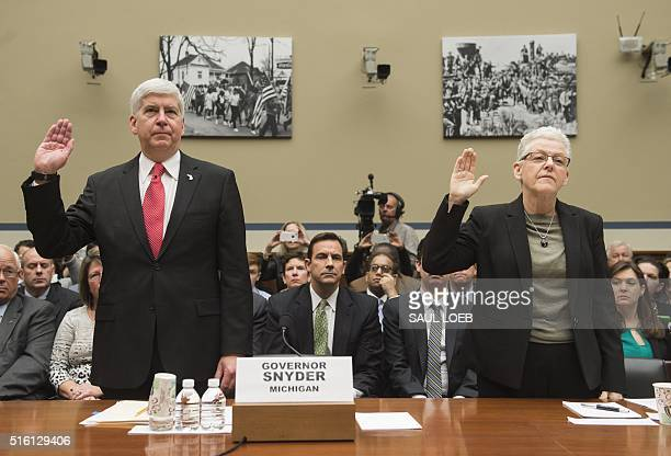 Michigan Governor Rick Snyder and Environmental Protection Agency Administrator Gina McCarthy raise their hands as they take the oath prior to...