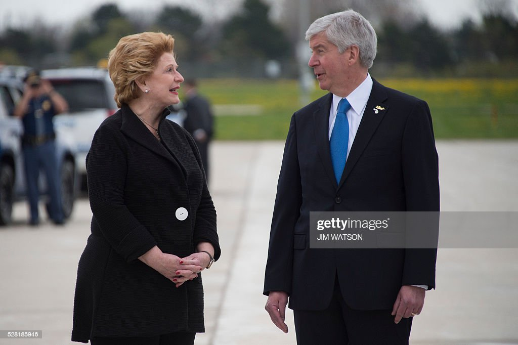 Michigan Governor Rick Synder (R) speaks with US Senator Debbie Stabenow (L), D-Michigan as they await the arrival of the US President at Bishop International Airport in Flint, Michigan, May 4, 2016. / AFP / Jim Watson