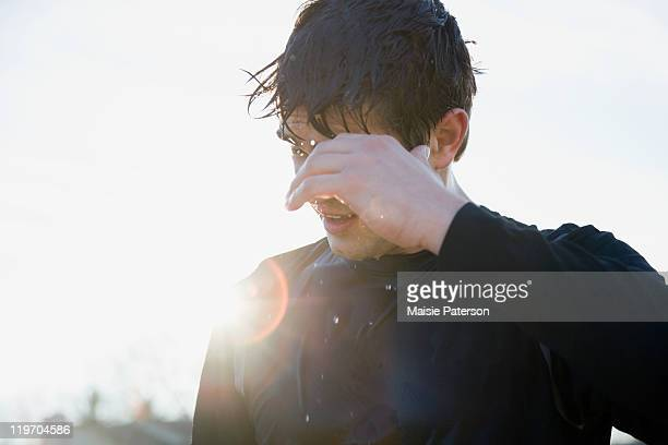 USA, Michigan, man in sports clothing back lit by sun