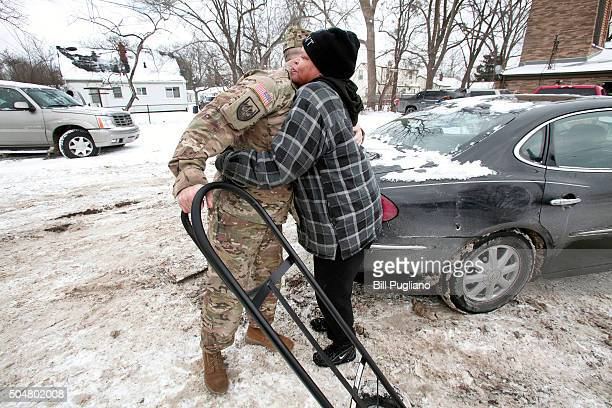 Michigan National Guard Staff Sergeant Steve Kiger of Beaverton Michigan gets a hug from Christine Brown of Flint Michigan after he helped her take...