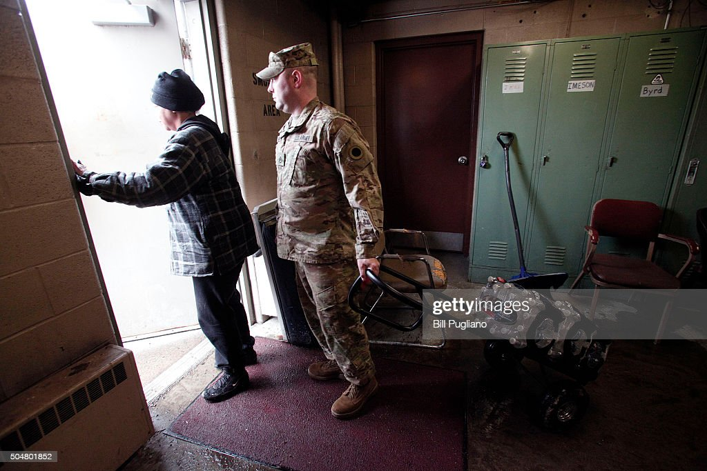 Michigan National Guard Staff Sergeant Steve Kiger of Beaverton, Michigan, helps Christine Brown of Flint, Michigan take bottled water out to her car after she received it at a Flint Fire Station January 13, 2016 in Flint, Michigan. On Tuesday, Michigan Gov. Rick Snyder activated the National Guard to help the American Red Cross distribute water to Flint residents to help them deal with the lead contamination that is in the City of Flint's water supply.