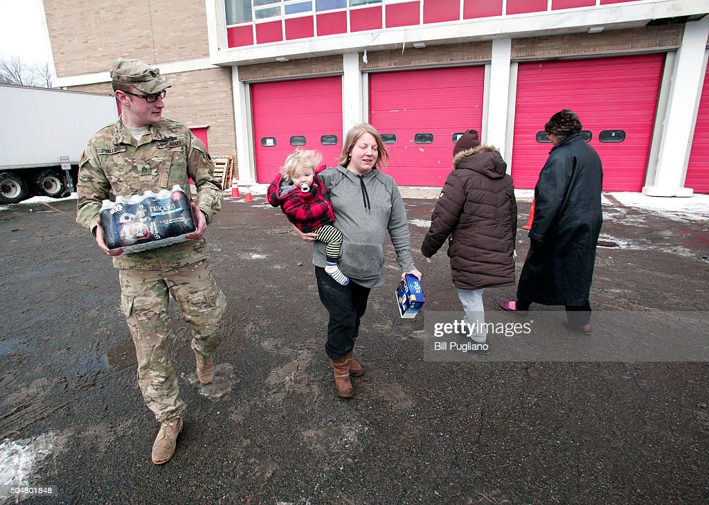 Michigan National Guard Staff Sergeant William Phillips of Birch Run, Michigan, helps Flint resident Amanda Roark and her son Dash take bottled water out to her vehicle after she received it at a Flint Fire Station January 13, 2016 in Flint, Michigan. On Tuesday, Michigan Gov. Rick Snyder activated the National Guard to help the American Red Cross distribute water to Flint residents to help them deal with the lead contamination that is in the City of Flint's water supply.