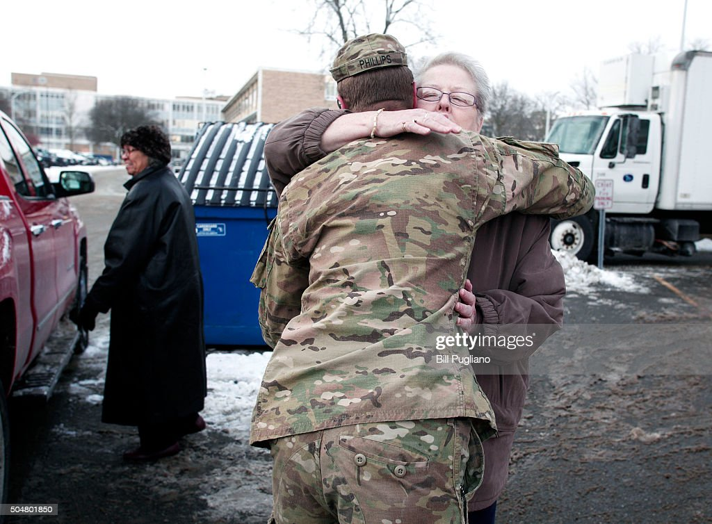 Michigan National Guard Staff Sergeant William Phillips of Birch Run, Michigan, gets hug from from a Flint resident after helping her take bottled water out to her car after she received it at a Flint Fire Station January 13, 2016 in Flint, Michigan. On Tuesday, Michigan Gov. Rick Snyder activated the National Guard to help the American Red Cross distribute water to Flint residents to help them deal with the lead contamination that is in the City of Flint's water supply.