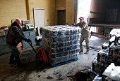 Michigan National Guard Staff Sergeant William Phillips of Birch Run Michigan helps a worker unload a pallet of bottled water at a Flint Fire Station...