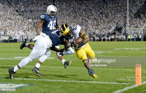 Michigan RB Karan Higdon crosses the goal line for a touchdown while being hit by Penn State LB Manny Bowen during the first half The Penn State...