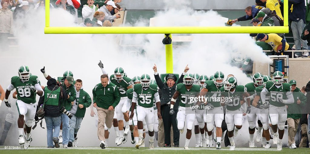 Michigan State head coach Mark Dantonio leads his team onto the field prior to the start of the game against the Michigan Wolverines at Spartan...