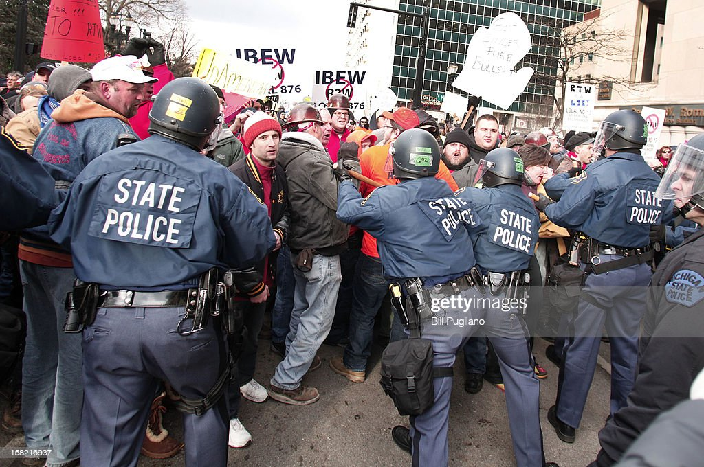 Michigan State Police in riot gear push back protestors who are blocking a street during a rally at the Michigan State Capitol to protest a vote on Right-to-Work legislation December 11, 2012 in Lansing, Michigan. Republicans control the Michigan House of Representatives, and Michigan Gov. Rick Snyder has said he will sign the bill if it is passed. The new law would make requiring financial support of a union as a condition of employment illegal.