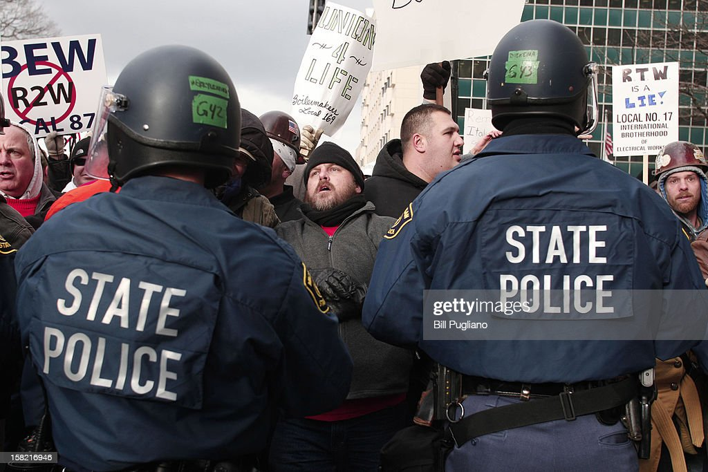 Michigan State Police in riot gear push have a stand-off with protestors who linked arms and blocked a street during a rally at the Michigan State Capitol to protest a vote on Right-to-Work legislation December 11, 2012 in Lansing, Michigan. Republicans control the Michigan House of Representatives, and Michigan Gov. Rick Snyder has said he will sign the bill if it is passed. The new law would make requiring financial support of a union as a condition of employment illegal.
