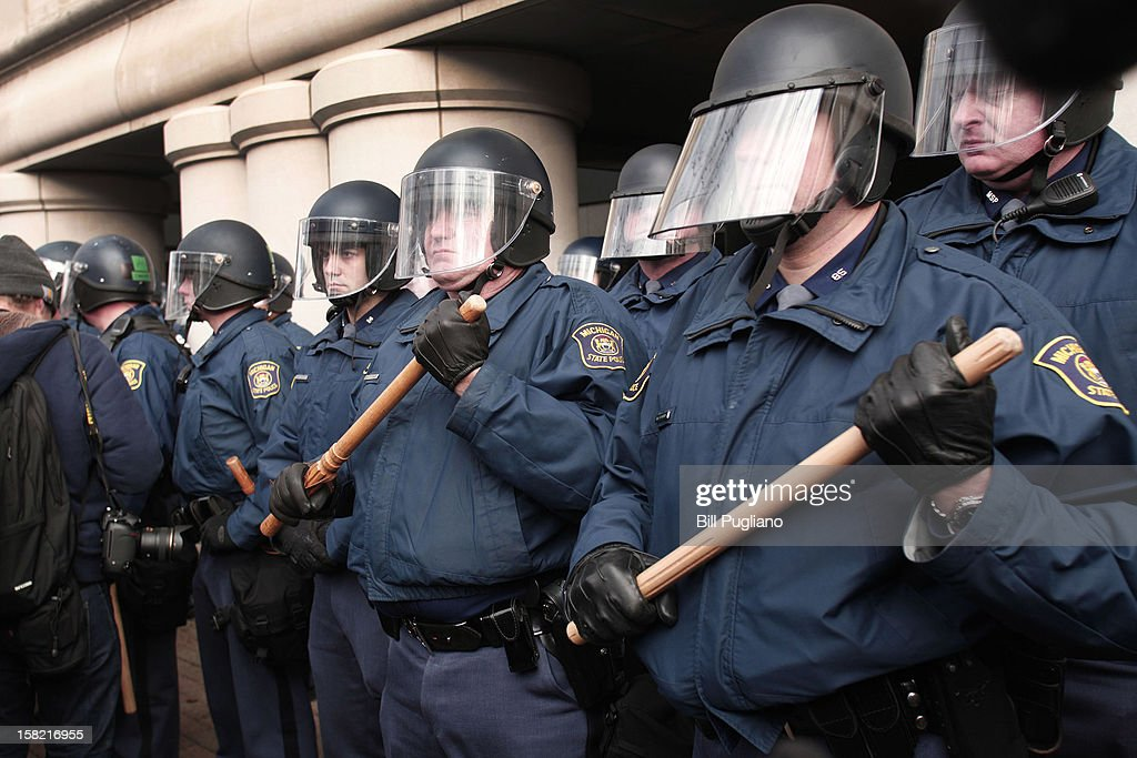 Michigan State Police in riot gear stand with batons at-the-ready while protestors linked arms and blocked a street during a rally at the Michigan State Capitol to protest a vote on Right-to-Work legislation December 11, 2012 in Lansing, Michigan. Republicans control the Michigan House of Representatives, and Michigan Gov. Rick Snyder has said he will sign the bill if it is passed. The new law would make requiring financial support of a union as a condition of employment illegal.