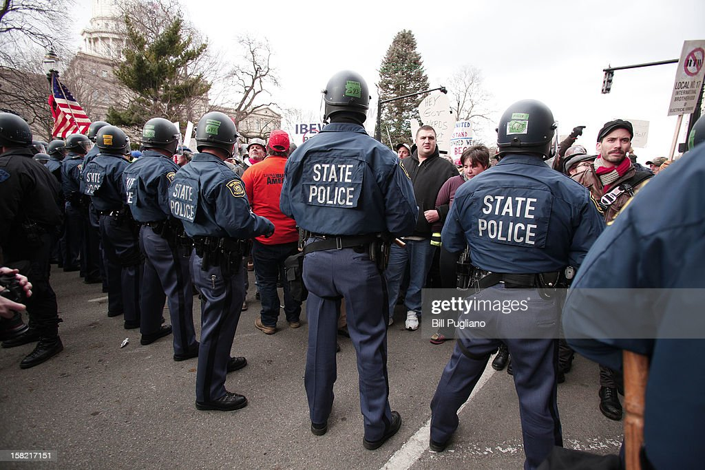 Michigan State Police in riot gear stand with batons while protestors block a street during a rally at the Michigan State Capitol to protest a vote on Right-to-Work legislation December 11, 2012 in Lansing, Michigan. Republicans control the Michigan House of Representatives, and Michigan Gov. Rick Snyder has said he will sign the bill if it is passed. The new law would make requiring financial support of a union as a condition of employment illegal.