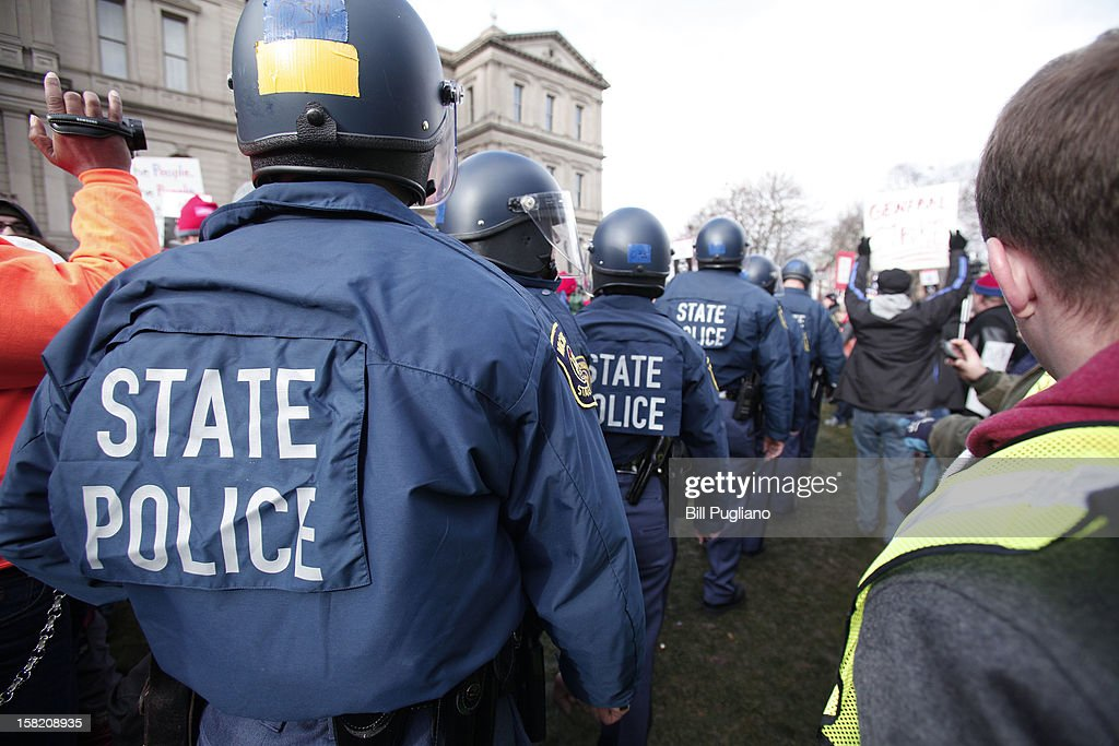 Michigan State Policewalk through the crowd of union members who gathered from around the country to rally at the Michigan State Capitol to protest a vote on Right-to-Work legislation December 11, 2012 in Lansing, Michigan. Republicans control the Michigan House of Representatives, and Michigan Gov. Rick Snyder has said he will sign the bill if it is passed. The new law would make requiring financial support of a union as a condition of employment illegal.