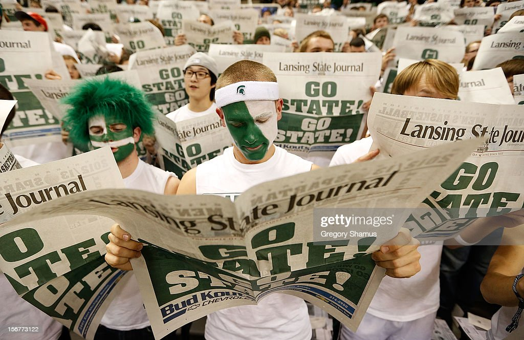 A Michigan State Spartans fans reads the paper while the starting lineup is introduced for the Boise State Broncos at the Breslin Center on November 20, 2012 in East Lansing, Michigan.