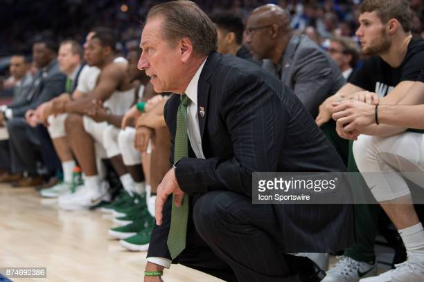 Michigan State Spartans head coach Tom Izzo kneels on the sidelines during the State Farm Champions Classic basketball game between the Duke Blue...