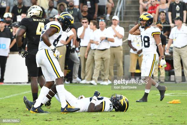 Michigan tight end Nick Eubanks lies injured on the turf after being hit in the head by Purdue safety Jacob Thieneman who was flagged for a personal...