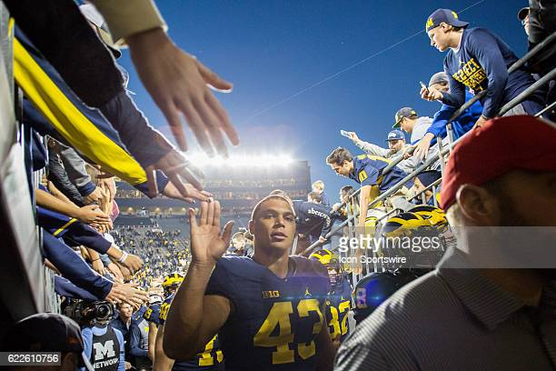 Michigan Wolverines defensive end Chris Wormley slaps hands with fans as he walks off of the field at the conclusion of the game between the Maryland...