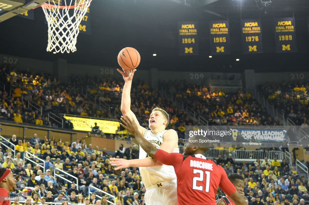 Michigan Wolverines forward Moritz Wagner (13) drives in for a layup past Rutgers Scarlet Knights forward Mamadou Doucoure (21) during the Michigan Wolverines game versus the Rutgers Scarlet Knights on Sunday January 21, 2018 at Crisler Center Field in Ann Arbor, MI.