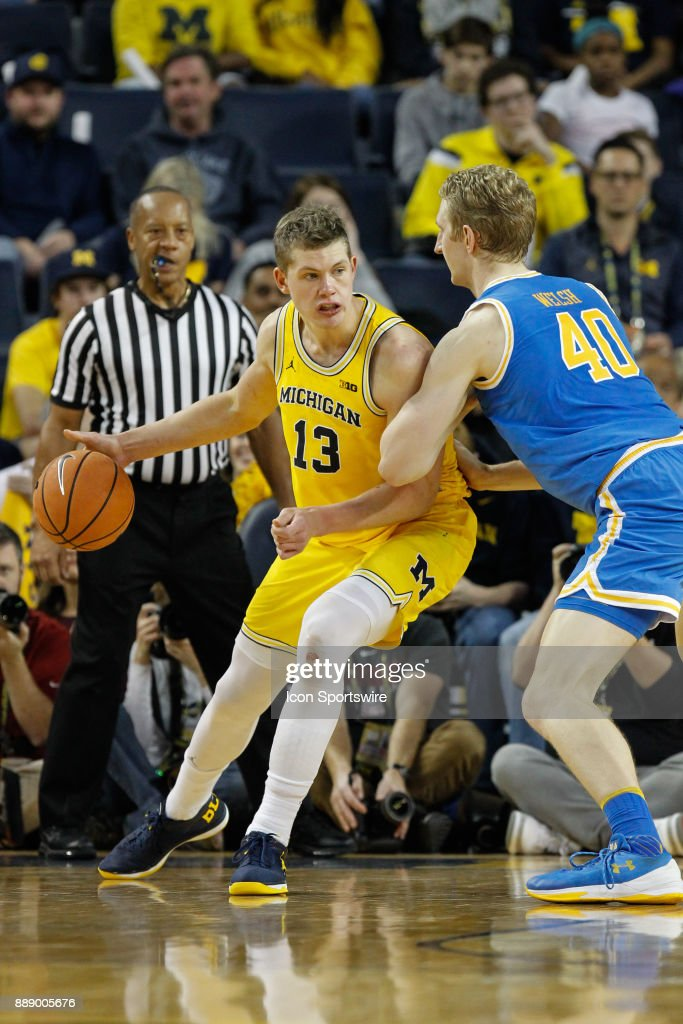 Michigan Wolverines forward Moritz Wagner (13) drives to the basket against UCLA Bruins center Thomas Welsh (40) during the second half of a regular season non-conference basketball game between the UCLA Bruins and the Michigan Wolverines on December 9, 2017 at the Crisler Center in Ann Arbor, Michigan. Michigan defeated UCLA 78-69 in overtime.
