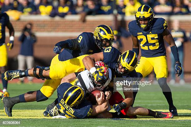 Michigan Wolverines linebacker Ben Gedeon and defensive end Chris Wormley make a tackle while Michigan Wolverines linebacker Mike McCray and safety...
