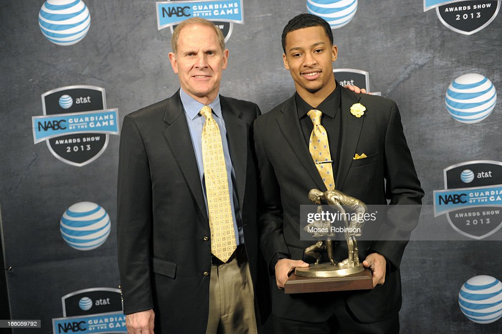 Michigan Wolverines Men's basketball John Beilein and Trey Burke pose with the 2013 Naismith Trophy at the NABC Guardians of the Game Awarding of the Naismith Trophy Presented by AT&T at Georgia World Congress Center on April 7, 2013 in Atlanta, Georgia.