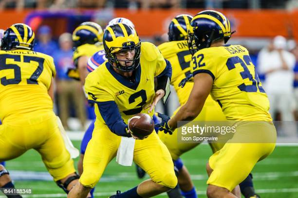 Michigan Wolverines quarterback Wilton Speight hands the football off to running back Ty Isaac during the game between the Michigan Wolverines and...