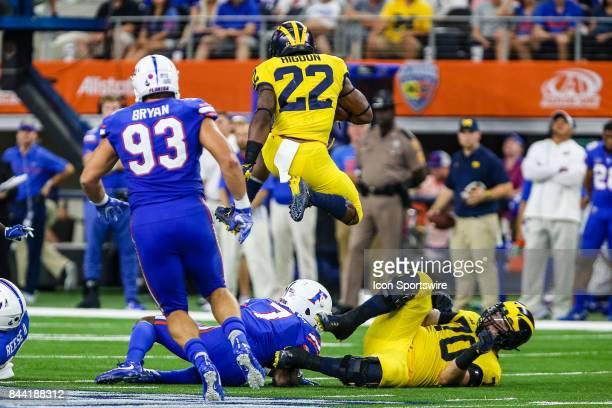 Michigan Wolverines running back Karan Higdon leaps over offensive lineman Nolan Ulizio and Florida Gators defensive back Duke Dawson during the game...