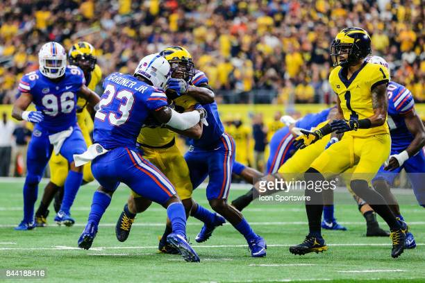Michigan Wolverines running back Ty Isaac runs through the line of scrimmage and gets tackled by Florida Gators defensive back Chauncey Gardner Jr...