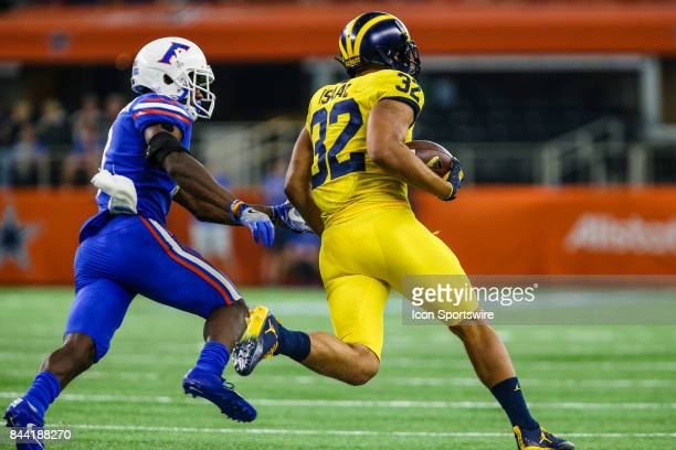 Michigan Wolverines running back Ty Isaac tries to outrun Florida Gators linebacker Jeremiah Moon during the game between the Michigan Wolverines and...