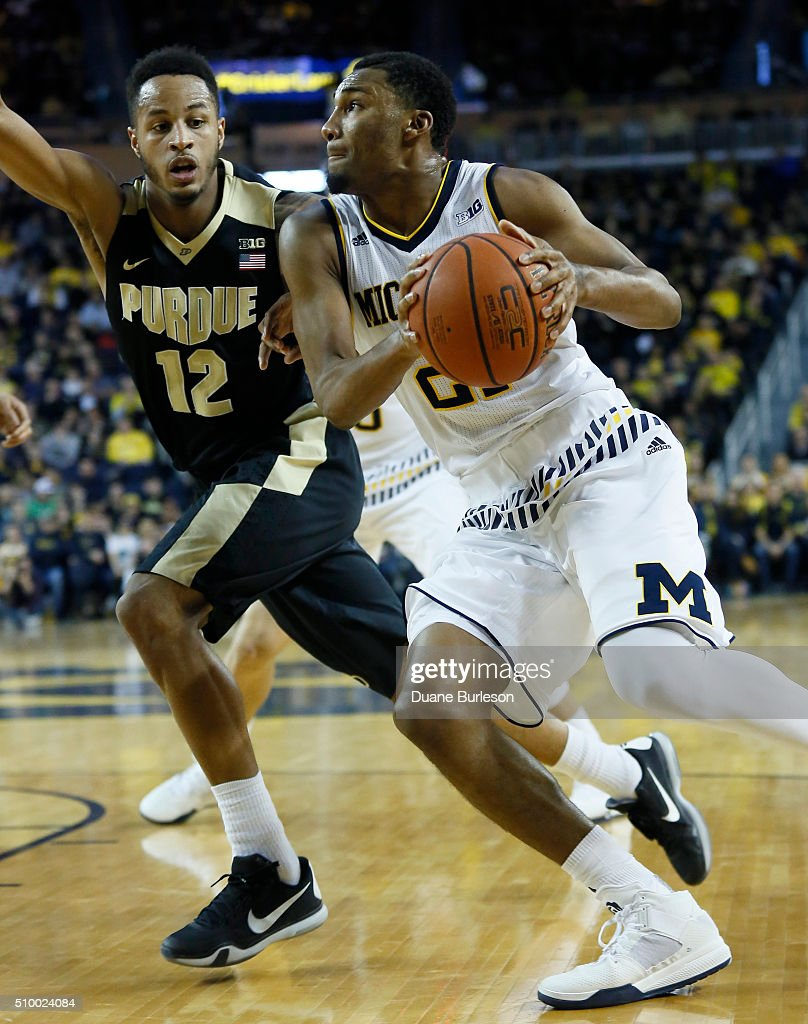 Michigan's Zak Irvin #21 drives to the basket against Vince Edwards #12 of the Purdue Boilermakers during the first half at Crisler Arena on February 13, 2016 in Ann Arbor, Michigan.