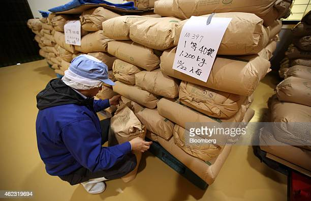 Michihiro Kono president of Yagisawa Shouten Co checks a bag of soy beans in a storage room at the company's factory in Ichinoseki Iwate prefecture...