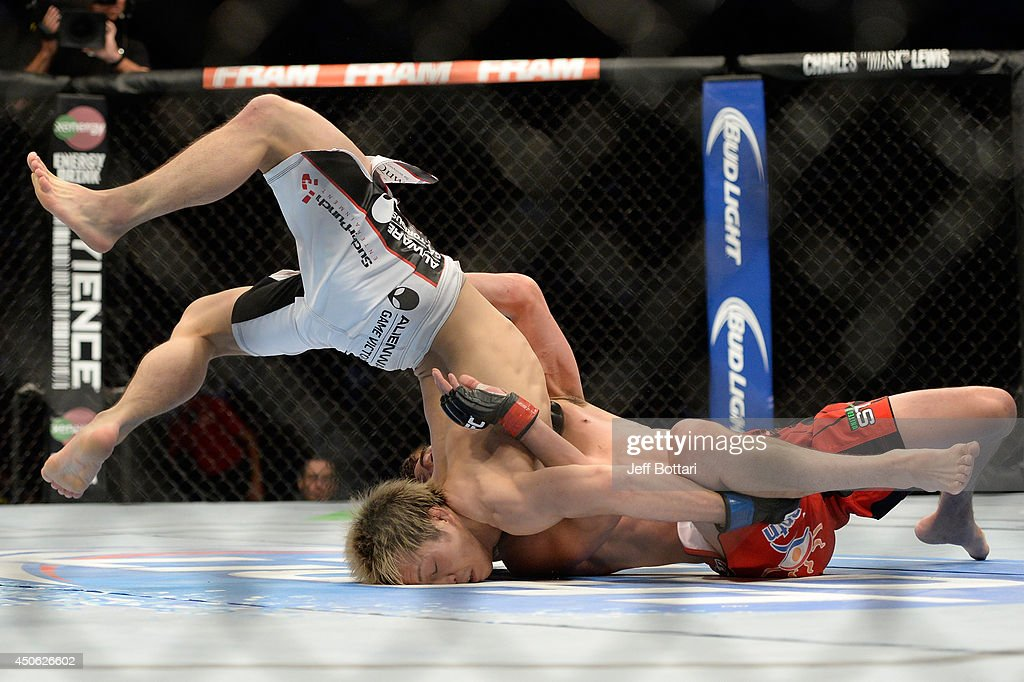 Michinori Tanaka is flipped over by Roland Delorme during the UFC 174 event at Rogers Arena on June 14, 2014 in Vancouver, British Columbia, Canada.
