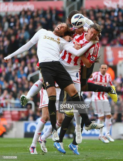Michu and Ashley Williams of Swansea City squeeze out Robert Huth of Stoke City during the Barclays Premier League match at the Britannia Stadium on...