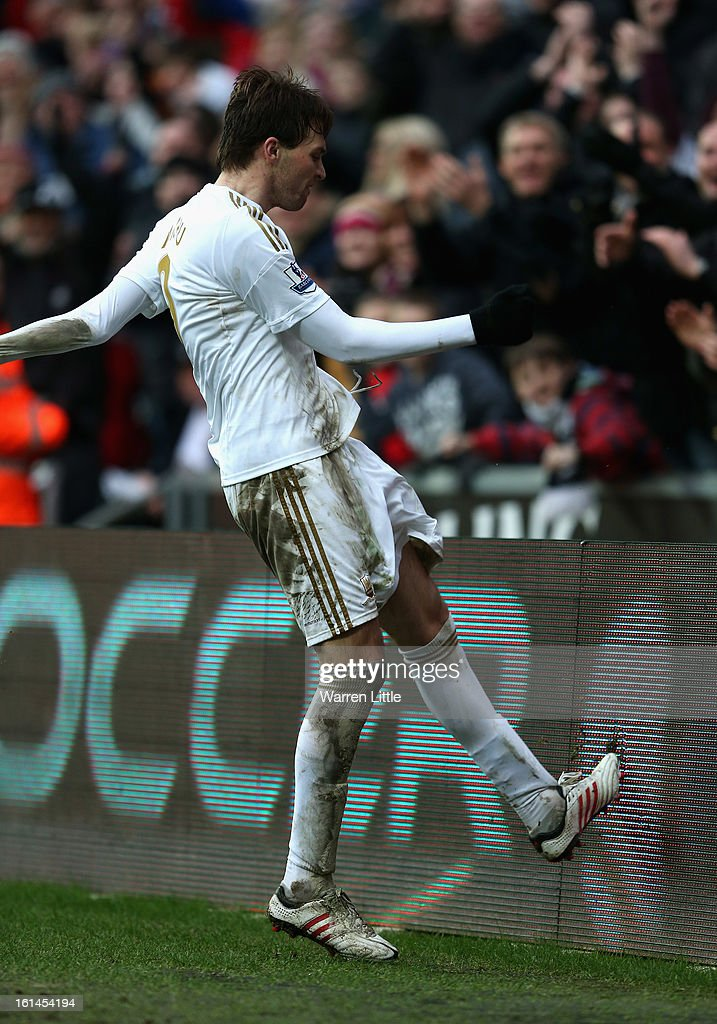 Michu of Swansea City kicks a abvertising board as he celebrates scoring the fourth goal during the Premier League match between Swansea City and Queens Park Rangers at Liberty Stadium on February 9, 2013 in Swansea, Wales.