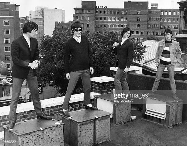 Mick Avory Ray Davies Dave Davies and Pete Quaife of the British rock band the Kinks standing on a London rooftop