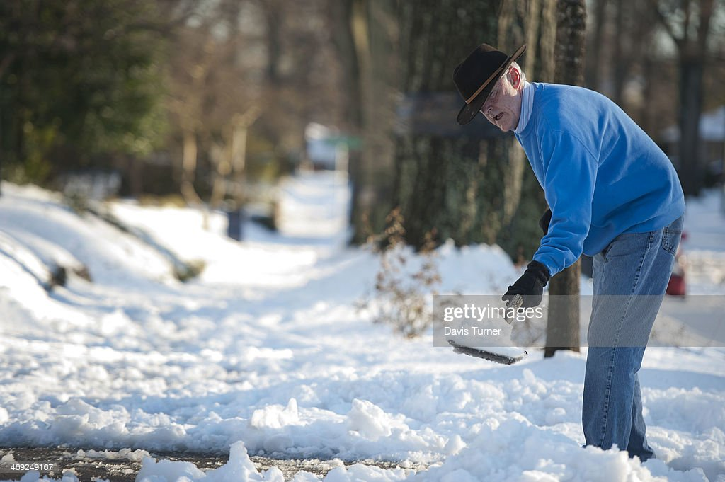 Mick Edwards shovels snow from his driveway on February 13 2014 in Charlotte North Carolina A snow storm moved through North Carolina the night...
