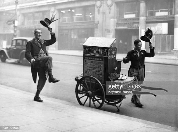 Mick et Mike en costumes de comédie musicale soulèvent leur chapeau lors d'un numéro de rue accompagnés par leur orgue de barbarie à Londres...