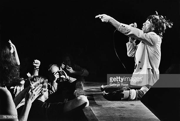 Mick Jagger lead singer of the British rock band The Rolling Stones gets down on his knees at the edge of the stage during a 1980 Atlanta Georgia...