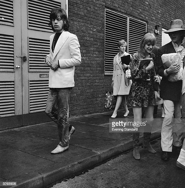 Mick Jagger left singer of the British rock group the Rolling Stones walks away from his girlfriend singer Marianne Faithfull and her friend leaving...
