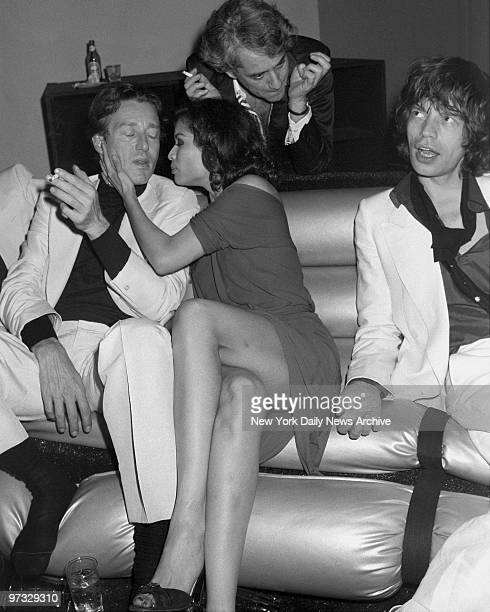 Mick Jagger looks unconcerned as his wife Bianca snuggles up to designer Halston during Bianca's birthday bash at Studio 54 in the wee hours of the...
