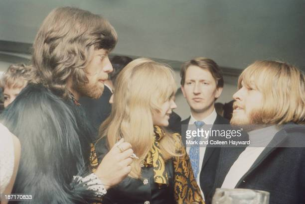 Mick Jagger Marianne Faithfull and Brian Jones from The Rolling Stones converse together at a party to celebrate the cabaret debut of the Supremes on...