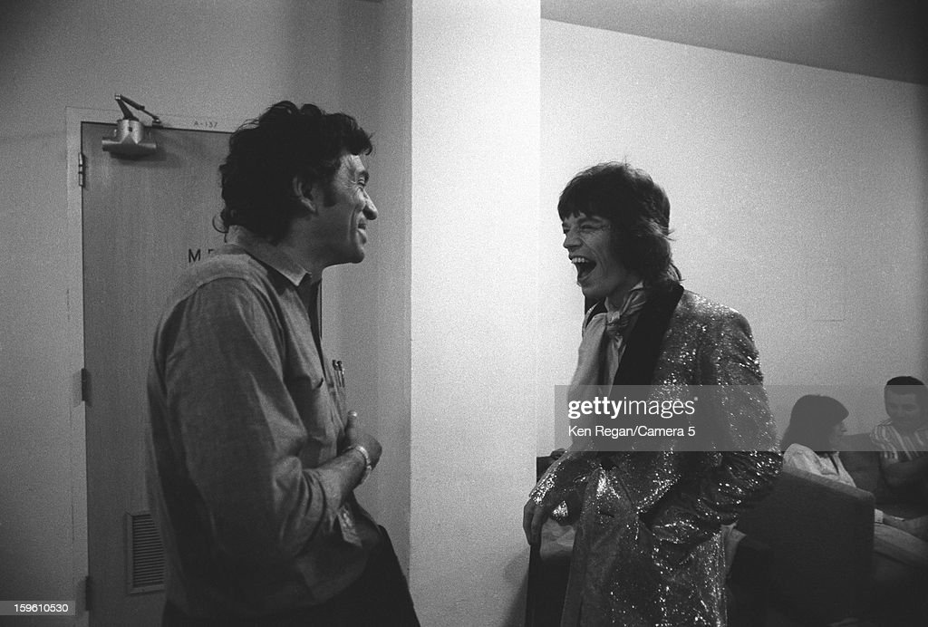 Mick Jagger of The Rolling Stones and musician Bill Graham are photographed sharing a laugh backstage in 1972 in Long Beach, California.