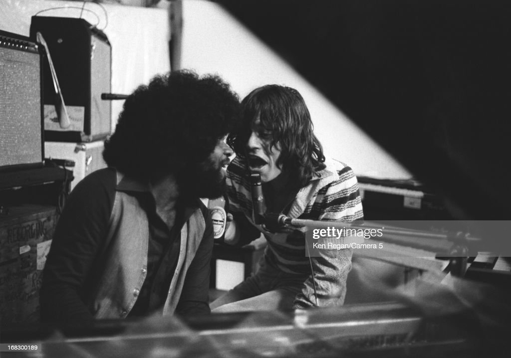 Mick Jagger of the Rolling Stones is photographed with sesison musician at artist Andy Warhol's home in 1975 in Montauk, New York.