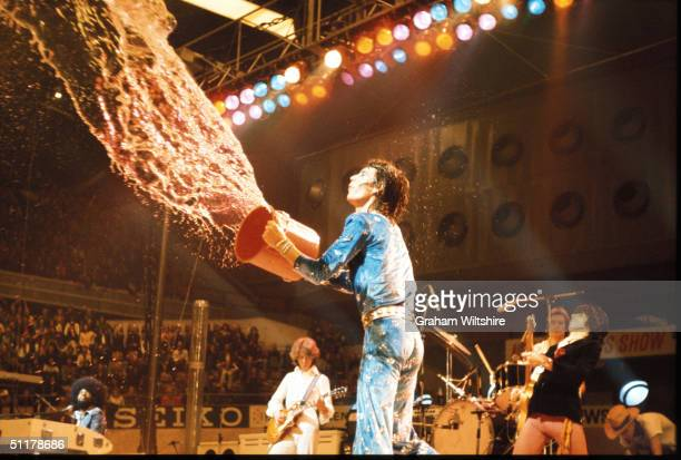 Mick Jagger of the Rolling Stones throws a bucket of water into the audience during the band's grand finale performance of 'Street Fighting Man' at...