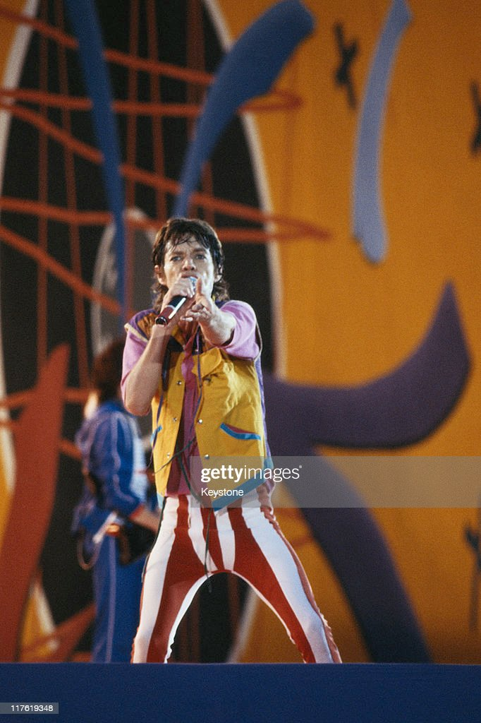 Mick Jagger singer with The Rolling Stones singing into a microphone on stage during a live concert performance by the band at Wembley Stadium in...