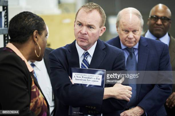 Mick Mulvaney director of the US Office of Management and Budget center holds a volume of the fiscal year 2018 budget while speaking with Davita...